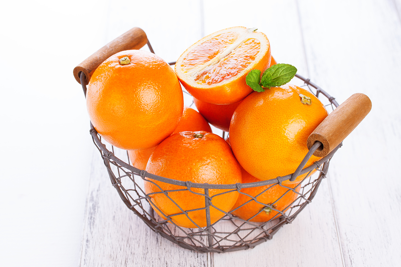 Fresh juicy summer blood oranges in a vintage basket with mint leaf on wooden table on a white background, closeup